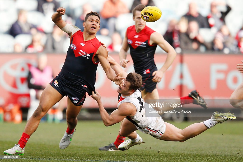 Neville Jetta of the Demons handballs as Maverick Weller of the Saints dives in an attempt to tackle during the round 17 AFL match between the Melbourne Demons and the St Kilda Saints at Melbourne Cricket Ground on July 26, 2015 in Melbourne, Australia.