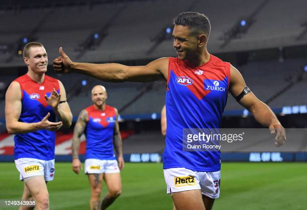 Neville Jetta of the Demons is congratulated by team mates after winning in his 150th game during the round 2 AFL match between the Carlton Blues and...