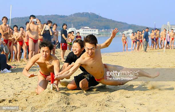 New 20 years old men wearing red 'Fundoshi' loincloths compete in the beach flag event during the winter swimming at the Tsuyazaki Beach on January...