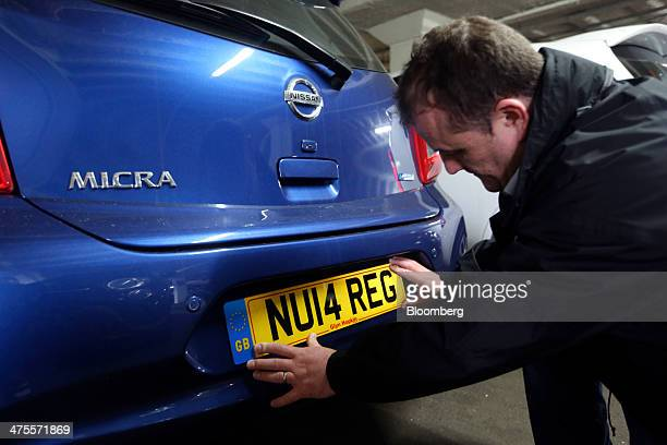 A new 2014 vehicle license registration plate sits prepared for a customer on the bumper of a Nissan Micra automobile produced by Nissan Motor Co in...