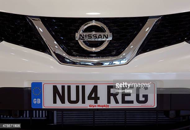 A new 2014 vehicle license registration plate sits prepared for a customer on the bumper of a Nissan Qashqai SUV automobile produced by Nissan Motor...