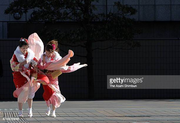 New 20yearold women wearing kimono walk in the strong wind to attends their comingofage ceremony on January 10 2011 in Tokyo Japan