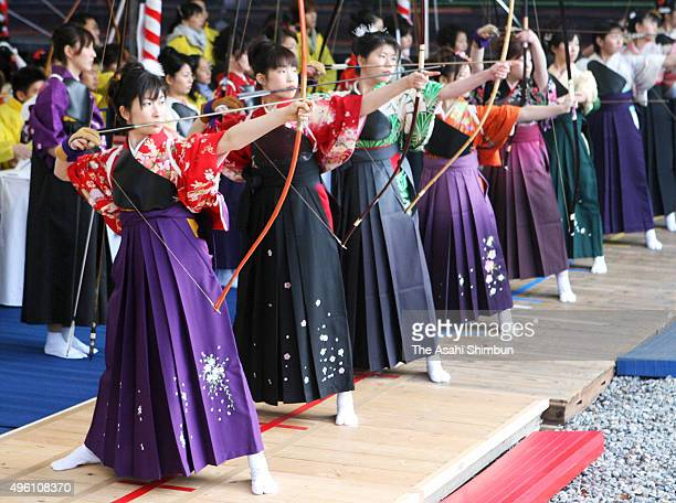 New 20yearsold wearing kimono take aim during an archery event to celebrate their comingofage at Sanjusangendo Temple on January 14 2014 in Kyoto...