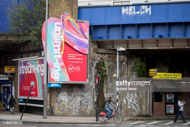 A new ads for Virgin Media fixed to an old Victorian wall beneath Waterloo station in SE1 on 19th August 2019 in London England
