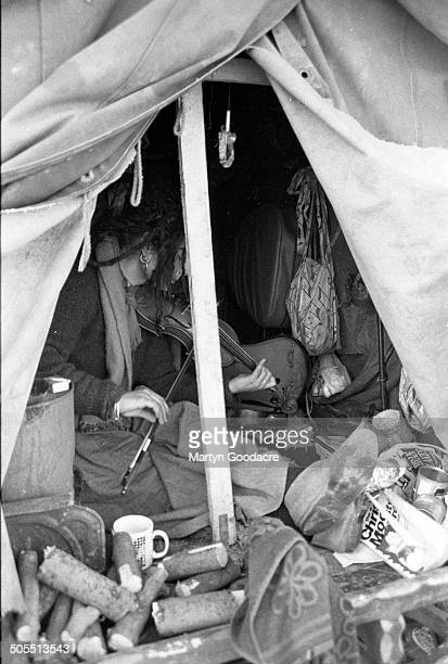 A New Age traveller playing the violin in a gipsy caravan at an encampment near Hereford 1987