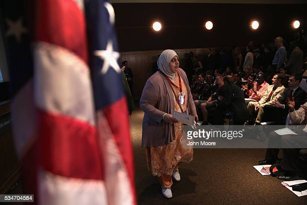 A new American citizen carries her certificate of citizenship during a naturalization ceremony on Ellis Island on May 27 2016 in New York City US...