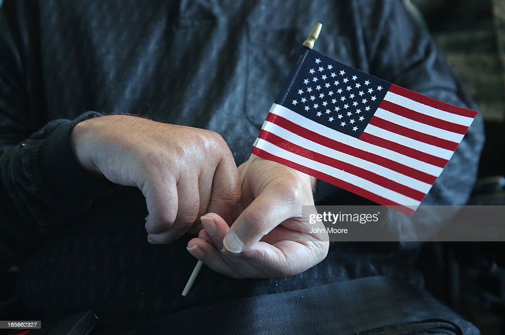 New American citizen John Cincar, 62, holds a U.S. flag after a ''homebound'' naturalization ceremony on October 25, 2013 in the Queens borough of New York City. Cincar, who was born in Yugoslavia and moved to the United States in 1965, has been a quadripelegic since falling at home in 2011 and now lives in the Midway Nursing Home. U.S. Citizenship and Immigration Services (USCIS), performs such on site naturalization ceremonies for immigrants with health issues and disabilities who have limited mobility. With his new American citizenship, Cincar says he plans to apply for a U.S. passport and, after further physical rehabilitation, hopes to travel back to his village near Belgrade, Serbia to visit family members he has not seen since his youth. He served in the U.S. Army from 1969-1972 as a supply clerk in Germany.