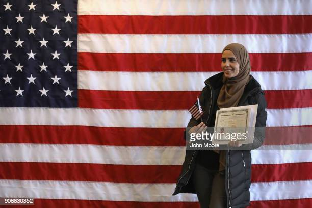 A new American citizen poses for photos following a naturalization service on January 22 2018 in Newark New Jersey Although much of the federal...