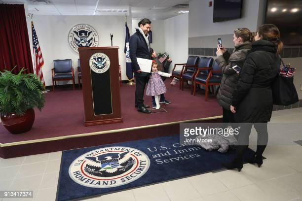 A new American citizen poses for photos with his family following a naturalization ceremony on February 2 2018 in New York City US Citizenship and...