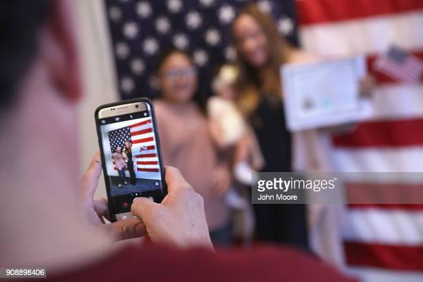 New American citizens pose for photos following a naturalization ceremony on January 22 2018 in Newark New Jersey Immigrants from 32 different...