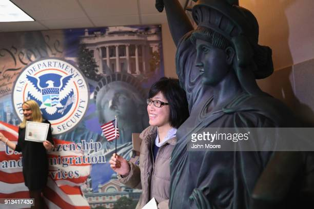 New American citizens pose for photos following a naturalization ceremony on February 2 2018 in New York City US Citizenship and Immigration Services...
