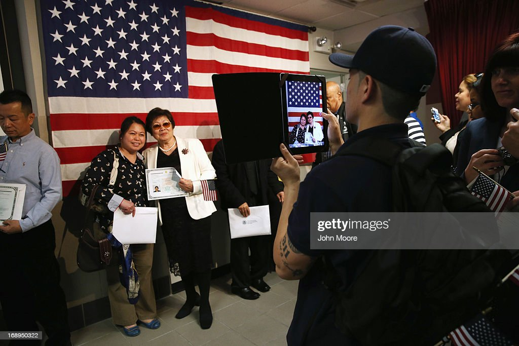 New American citizens take photos with their citizenship certificates following a naturalization ceremony at the U.S. Citizenship and Immigration Services (USCIS), office on May 17, 2013 in New York City. One hundred and fifty immigrants from 38 different countries became U.S. citizens at the event. Some 11 million undocumented immigrants living in the U.S. stand to eventually gain American citizenship if Congress passes immigration reforms currently being negotiated in Washington D.C.