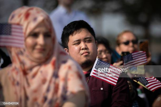 New American citizens wave American flags while 'America The Beautiful' is sung during a naturalization ceremony at Liberty State Park October 2 2018...