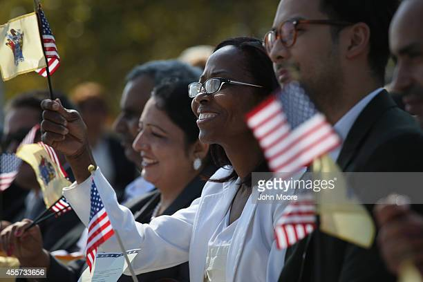 New American citizens wave flags after taking the oath of citizenship to the United States at a naturalization ceremony at Liberty State Park on...