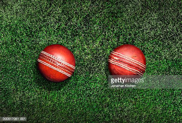 New and old cricket ball on grass, elevated view, (digital composite)