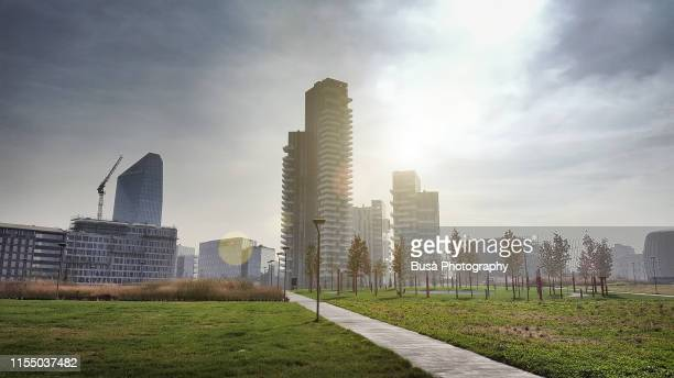 new architectures and highrise developments (including the apartment towers of torre solaria) as seen from the public park biblioteca degli alberi in the porta nuova district of milan, italy - milano foto e immagini stock