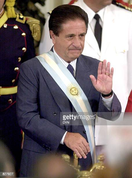 New Argentine President Eduardo Duhalde waves as he wears the presidential sash January 2 2002 at the Casa Rosada government house in Buenos Aires...