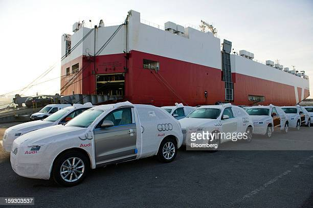New Audi AG automobiles stand beneath protective covers on the dockside beside the Le Mans Express roll on roll off ship at Barcelona port in...