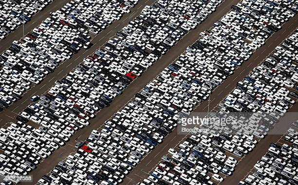 New automobiles covered in protective wrapping sit on the dockside at the Port of Tilbury operated by Forth Ports Plc in this aerial photograph taken...