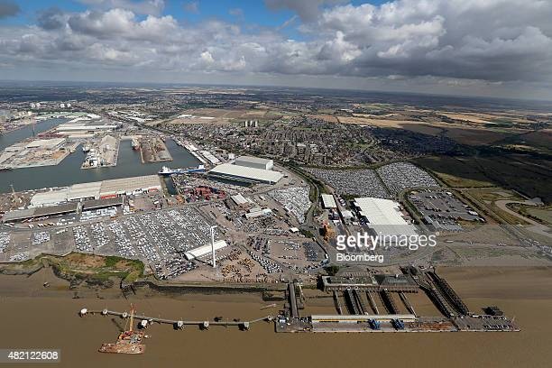 New automobiles covered in protective wrapping sit on the dockside the Port of Tilbury operated by Forth Ports Plc in this aerial photograph taken...