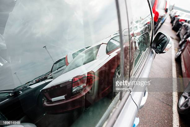 New automobiles manufactured by Volvo Cars are reflected in a window as they stand on the dockside before shipping at the Port of Gothenburg in...