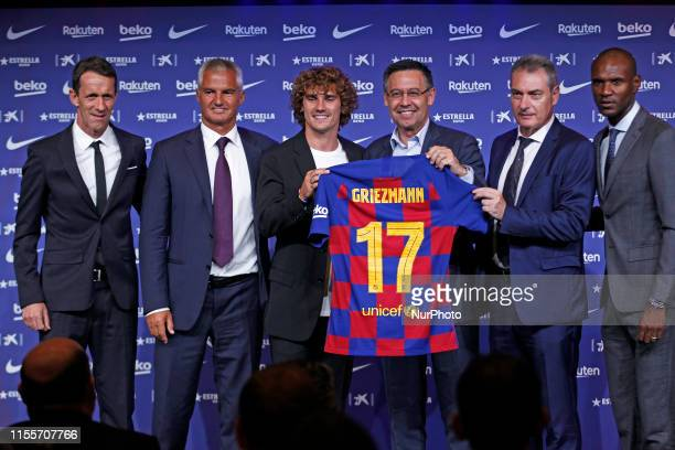 New Barcelona signing Antoine Griezmann poses for the media with FC Barcelona president Josep Maria Bartomeu Eric Abidal and other officials during...