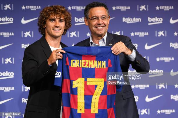 New Barcelona signing Antoine Griezmann poses for the media with FC Barcelona president Josep Maria Bartomeu as he is unveiled at Camp Nou stadium on...