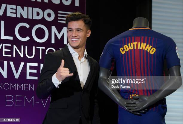 New Barcelona signing Philippe Coutinho poses for a photograph next to his new shirt as he is unveiled at Camp Nou on January 8 2018 in Barcelona...