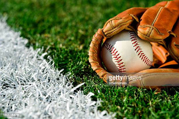 new baseball in glove along foul line - baseball glove stock pictures, royalty-free photos & images
