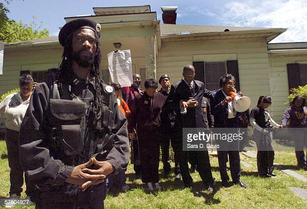 New Black Panther Party member stands guard outside the home where a private dancer alleges she was raped by Duke lacrosse team members during the...