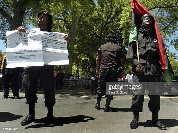 New Black Panther Party members hold a PanAfrican also known as a Black Liberation Flag and the eight demands they have in regards to the Duke...