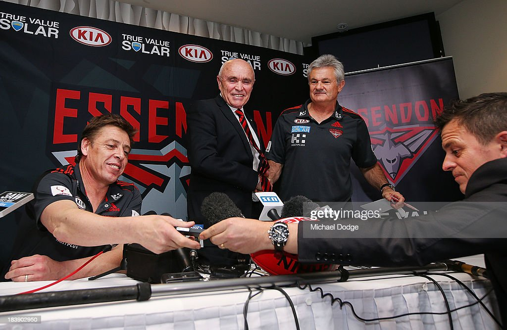 New Bombers coach Mark Thompson reacts next to Chairman Paul Little and new Senior assistant coach Neil Craig when getting his mobile phone handed back to him by a journalist after he dropped it during an Essendon Bombers AFL press conference at Windy Hill on October 10, 2013 in Melbourne, Australia.