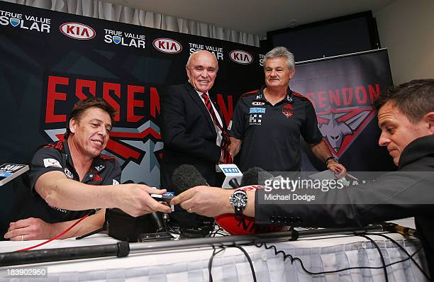 New Bombers coach Mark Thompson reacts next to Chairman Paul Little and new Senior assistant coach Neil Craig when getting his mobile phone handed...