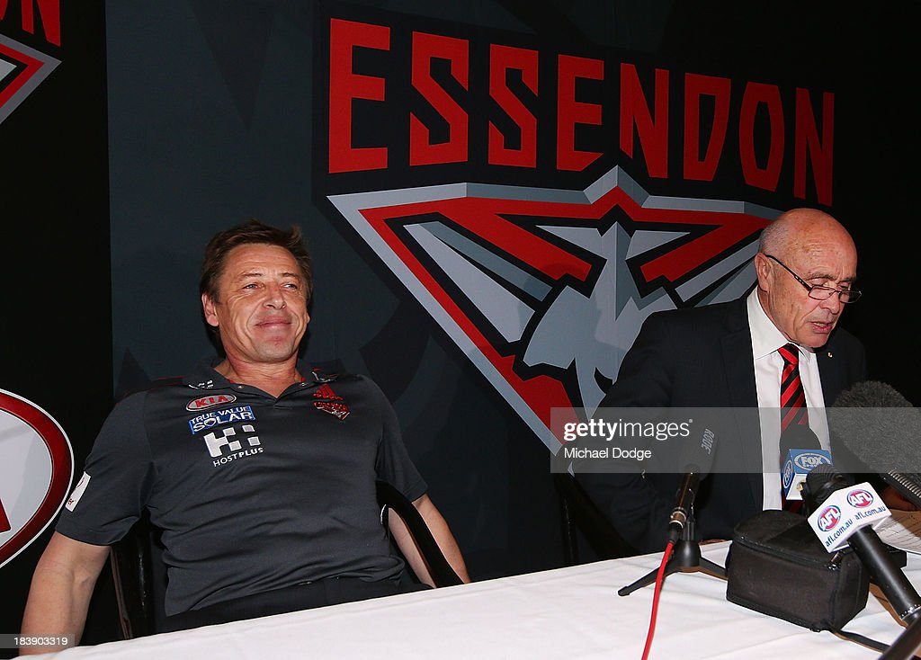 New Bombers coach Mark Thompson reacts next to Chairman Paul Little after dropping his mobile phone during an Essendon Bombers AFL press conference at Windy Hill on October 10, 2013 in Melbourne, Australia.
