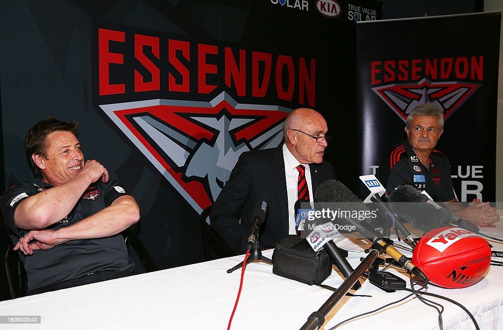 New Bombers coach Mark Thompson reacts next to Chairman Paul Little and new Senior assistant coach Neil Craig after dropping his mobile phone during an Essendon Bombers AFL press conference at Windy Hill on October 10, 2013 in Melbourne, Australia.