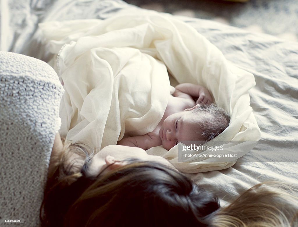 New born baby and mother resting in bed : Stockfoto