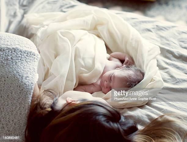 New born baby and mother resting in bed