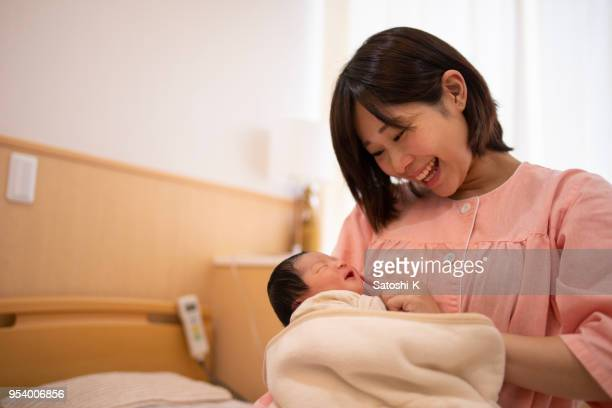New born baby and mother smiling in hospital