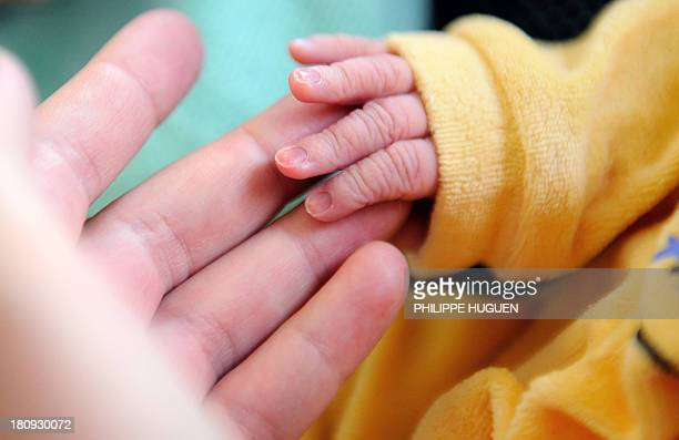 A new born baby takes the finger of his mother after the delivery on September 17 2013 at the Lens hospital northern France AFP PHOTO PHILIPPE HUGUEN