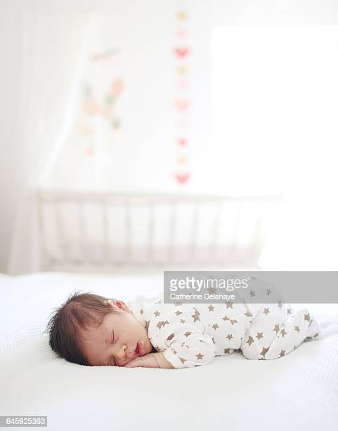 A new born sleeping on a bed