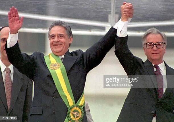 New Brazilian President Fernando Henrique Cardoso waves after receiving the presidential sash from outgoing President Itamar Franco 01 January 1995...
