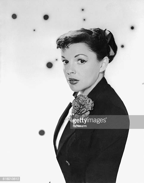 New bride with a new hairdo, and happier and sprightlier than ever is Judy Garland, shown in the first informal portraits she has posed for in...
