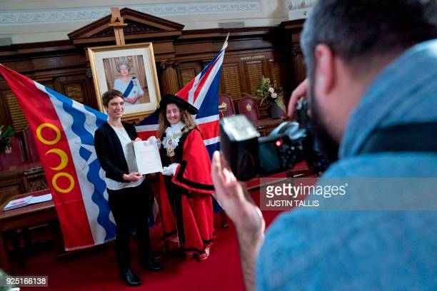 New British citizen Spanish charity worker Almudena Lara poses for her official photograph with her certificate of naturalisation during a...