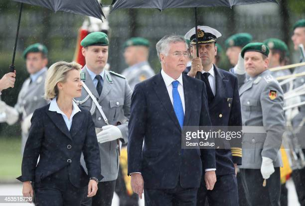 New British Defence Secretary Michael Fallon and German Defence Minister Ursula von der Leyen review a guard of honour under rain upon Fallon's...