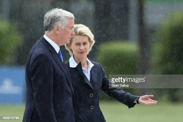 New British Defence Secretary Michael Fallon and German Defence Minister Ursula von der Leyen prepare to review a guard of honour under rain upon...
