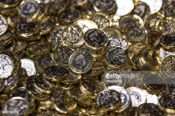New British one pound coins sit in a container during their production at The Royal Mint in Llantrisant UK on Thursday March 23 2017 Britain's Royal...