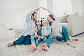 New building residential house purchase apartment concept. Stylish full family with two kids sitting on carpet, mom and dad making roof figure with hands arms over heads