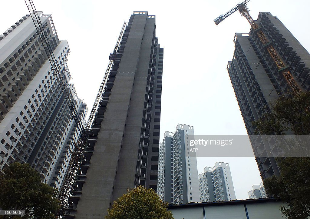 New buildings stand on a construction site in Yichang, central China's Hubei province on December 18, 2012. The cost of new homes increased in more Chinese cities in November than in the previous month, official figures showed on December 18, despite efforts from the government to keep the market in check. CHINA