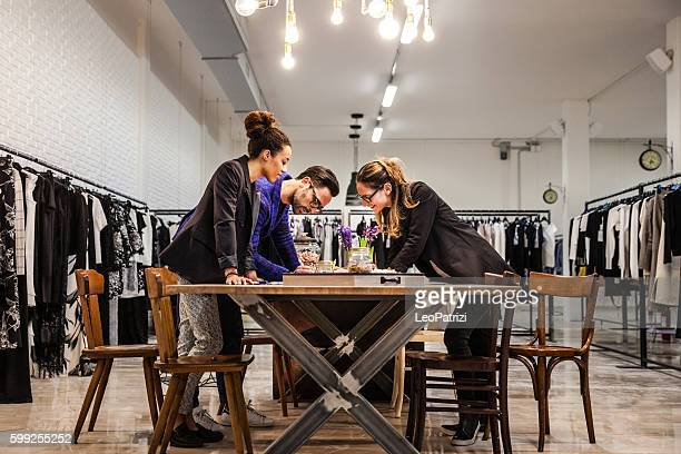 new business clothing store, team at work on new arrivals - fashion showroom stock pictures, royalty-free photos & images