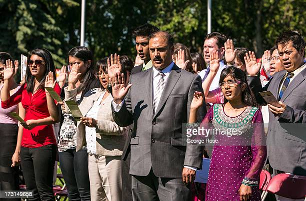 New Canadian citizens are sworn in during an immigration ceremony on the grounds of the Alberta Legislature on Canada Day on July 1 2013 in Edmonton...